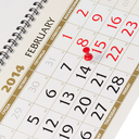 Calendar page with red thumbtack on February 14 2014. Closeup.