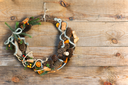 Green Christmas Wreath with Decorations on Wooden Background. Closeup.