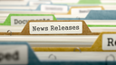 File Folder Labeled as News Releases in Multicolor Archive. Closeup View. Blurred Image.