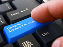 Consumer Behaviour Analysis - Written on Blue Keyboard Key. Male Hand Presses Button on Black PC Keyboard. Closeup View. Blurred Background.