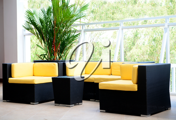 Hotel deck interior furniture with black sofa and chairs and yellow pillows