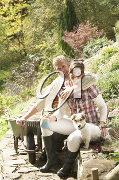 Couple With Dog Having Coffee Break Whilst Working Outdoors In Garden