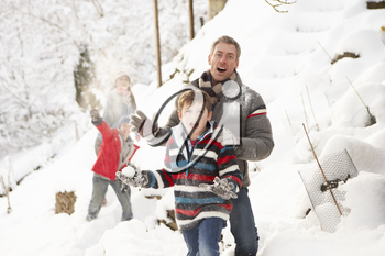 Family Having Snowball Fight In Snowy Landscape