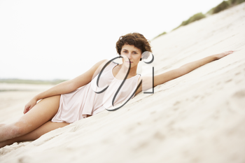 Fashionably Dressed Attractive Young Woman Laying Amongst Sand Dunes