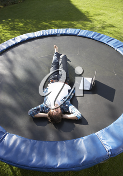 Young Man Relaxing On Trampoline With Laptop