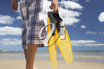 Teenage boy on beach with flippers