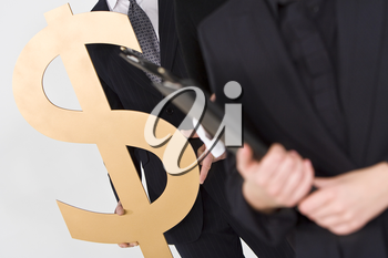 Concept shot showing business people standing in a line, the last of whom is carrying a large golden dollar symbol