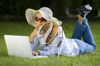 A beautiful young woman using her laptop in a park and bathed in summer sunshine