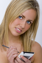 A beautiful blond haired blue eyed woman using her PDA