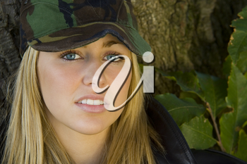 A beautiful blonde haired blue eyed young woman wearing a camouflage cap