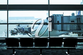 Waiting area of airport gate with airplane outside