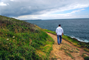 A man walking on a hiking trail along the coast of Brittany, France