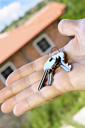 Man's hand holding keys with a house under construction in background