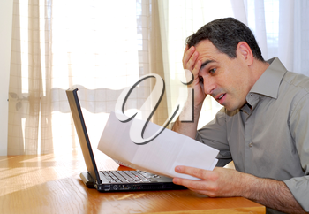 Man sitting at a desk looking at bills with horror