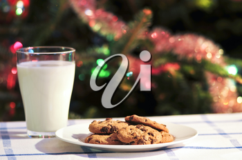 Plate of cookies and glass of milk near Christmas tree