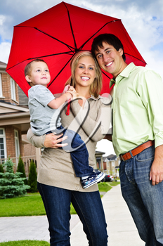 Young happy family under umbrella on sidewalk