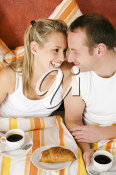 Couple having breakfast in bed in the morning