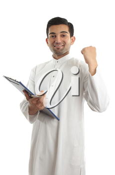 happy ethnic businessman wearing traditional robe, durta, dishdasha, holding a file folder and with hand clenched in a victorious fist.