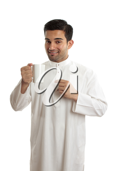 Smiling ethnic arab man wearing a robe, thobe, Kurta, dishdasha, etc.   He is enjoying a cup of coffee.  The coffee bean plant was first recognized in Yemen in Arabia and the north east of Ethiopia, a