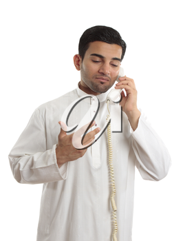 A middle eastern arab business man wearing an embroidered white kurta, thobe, robe, tunic, etc with ruby gemstone buttons, talks on a standard telephone