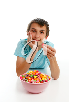 A boy relaxing with a large bowl of colourful popcorn.  White background.