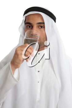 An arab middle eastern man wearing traditional clothing, is drinking a tall glass of clean fresh water. Water shortage stress from an increasing arab population and climate change compounding the prob