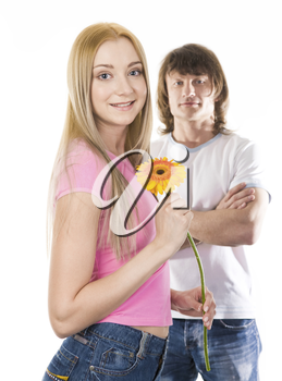 Image of cute girl with beautiful herbera looking at camera on background of her boyfriend