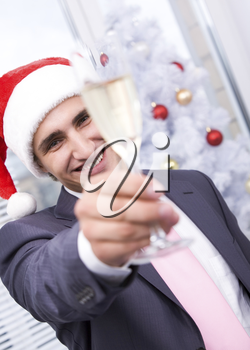 Portrait of handsome businessman stretsching flute with champagne and smiling at camera