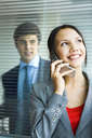Portrait of pretty business woman talking by mobile phone and looking at camera with smile
