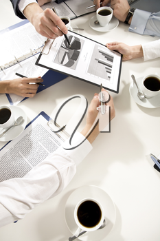 Above angle of businesspeople�s hands holding documents, papers with cups of coffee near by