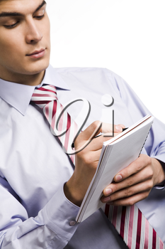 Close-up of male writing something in notepad over white background