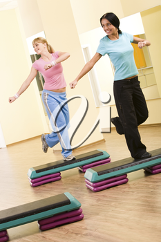 Two sporty women practicing physical exercises standing on one leg and looking to the right