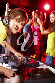 Smart deejay looking at camera with dancing teens on background