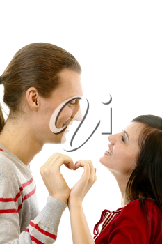 Portrait of attractive girl and her boyfriend looking at each other while making shape of heart by their hands