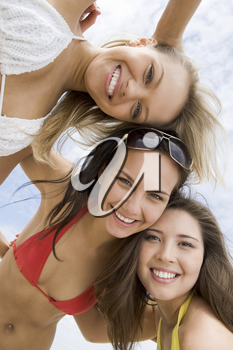 Portrait of happy girls in bikini embracing each other and looking at camera