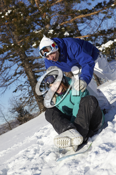 Portrait of happy dates snowboarding during winter vacations
