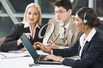 Team of three young business people gathered together around the laptop discussing a project