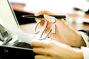 Close-up of businesswoman�s hands holding a pen and a document over the laptop in the office