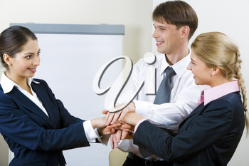 Portrait of three smiling business partners with a pile of their hands and looking at each other on the background of whiteboard in the office