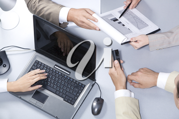 Close-up of business people hands working with laptop, documents and calling on cell