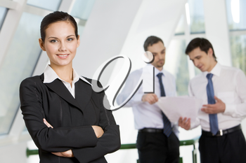 Portrait of attractive business lady looking at camera with smile on background of interacting men