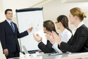 Photo of happy businessman standing by whiteboard while partners applauding to him after successful presentation