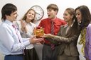Portrait of friendly colleagues giving birthday present to happy man in office
