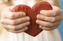 Close-up of red wooden heart in child�s hands showing it