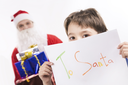 Photo of curious brown-eyed boy peeking out of his letter to Santa Clause