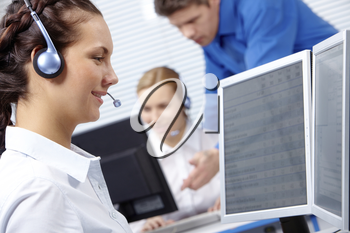 Portrait of consultant speaking by headset and looking at monitor of computer