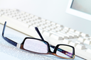 Image of eyeglasses at workplace with paper and keyboard near by