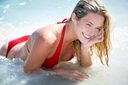 Portrait of pretty girl in red swimsuit lying in the sea