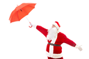 Photo of confused Santa Claus stretching arm with red umbrella in isolation