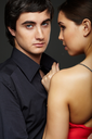 Portrait of handsome man looking at camera with beautiful woman near by